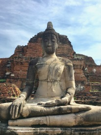 A peaceful Buddha in front of the temple ruins
