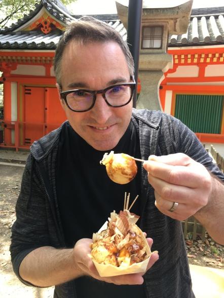 Todd enjoys some takoyaki (breaded octopus) at a local shrine